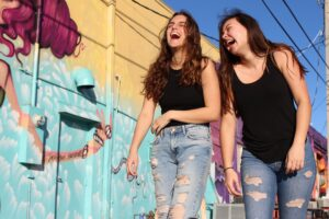 Clarinet Humor Photo Of Two Laughing Women Walking Past Graffiti Wall 2346701